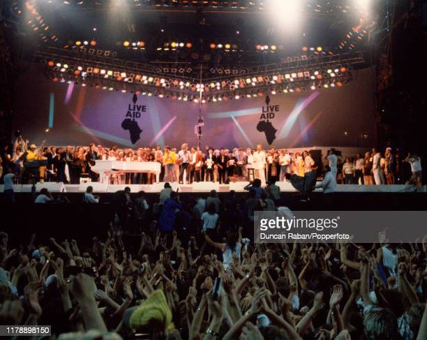 A view of the crowd and the stage as all the acts gather to perform the Band Aid single Do They Know It's Christmas during the finale of the Live Aid...