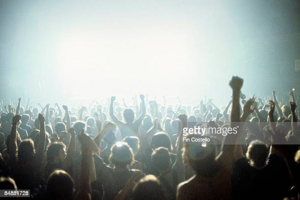 A view of the crowds at a rock concert from the back of a venue looking to a bightly lit stage over the heads and raised arms of a cheering audience...