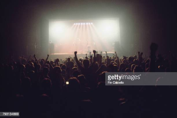 A view of the crowds of fans during the encore finale of a rock concert from the back of a venue looking to a bightly lit stage over the heads and...