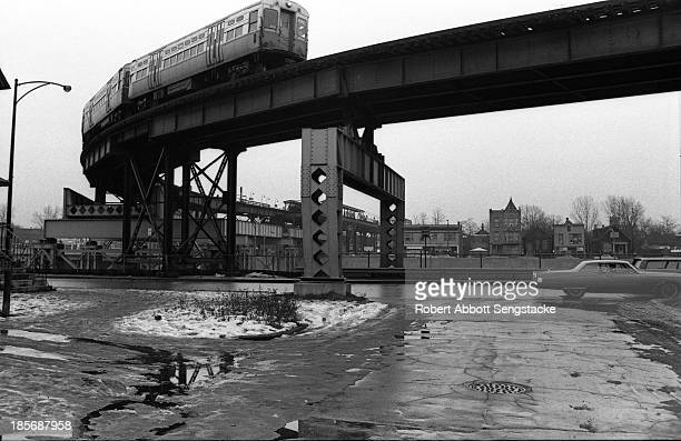 View of the curved track of an elevated railway, or the El, upon which a trian rolls past, Chicago, Illinois, 1960s.