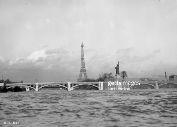 View of the Eiffel Tower and the Pont de Grenelle across the river Seine , Paris, France, March 1919. Also visible is a replica of 'Liberty...