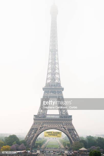 View of the Eiffel Tower with a banner reading 'liberty equality fraternity' hung by Greenpeace activists to protest against the farright Front...