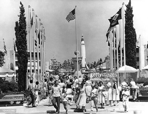 View of the entrance to Disneyland decorated with flags In the background a rocketship can be seen Located near Los Angeles Disneyland was the first...