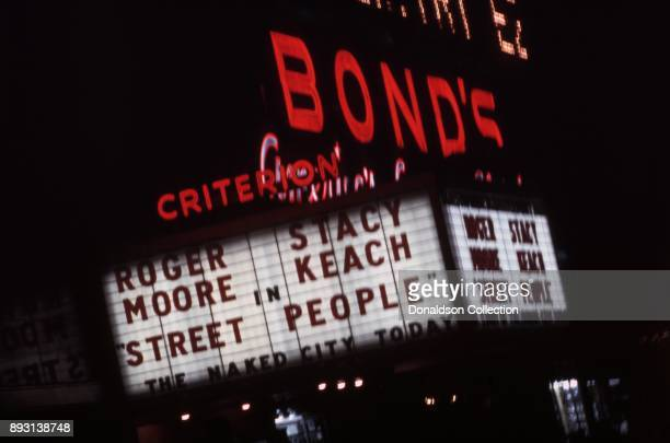 A view of the exterior of the Criterion Theatre on West 42nd Street with the films 'Street People' on the marquee with ads above for Gordon's Gin...