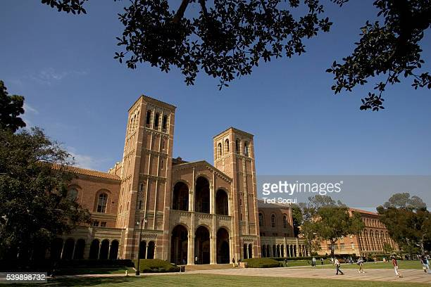 View of the facade of Royce Hall with students walking on the grounds of the UCLA College Campus.