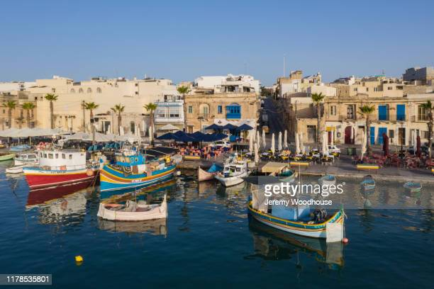 view of the fishing port of marsaxlokk from the harbour - marsaxlokk stock pictures, royalty-free photos & images
