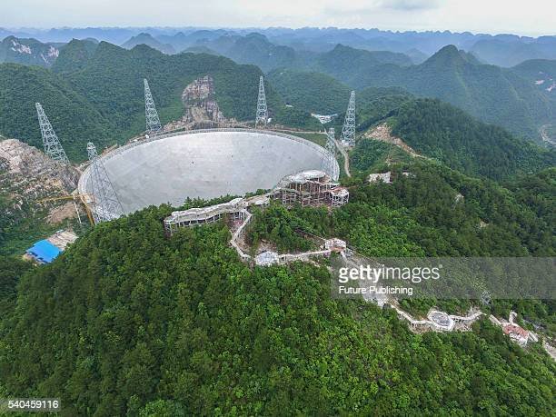 A view of the Fivehundredmeter Aperture Spherical radio Telescope near its completion on June 13 2016 in the remote Pingtang county China The project...