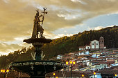 View of the fountain with San Cristobal church in the background. Plaza de Armas, Cusco, Peru, South America
