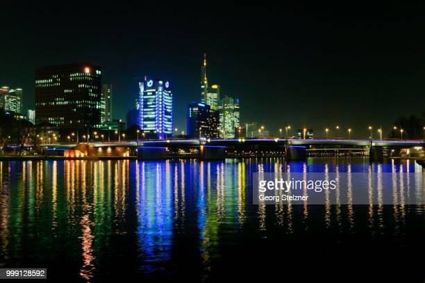 View of the Frankfurt skyline with blue-lit Union Investment building, the yellow-lit Commerzbank tower, IG Metall headquarters, life at front, and Friedensbruecke, from the south-west bank of the Main river at night, Frankfurt am Main, Hesse, Germany