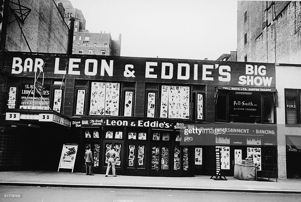 View of the front of Leon & Eddie's night club from across West 52nd Street, New York, New York, late 1930s. A serviceman and a civilian look at photographs of the entertainers, plastered all across the doorways and windows.