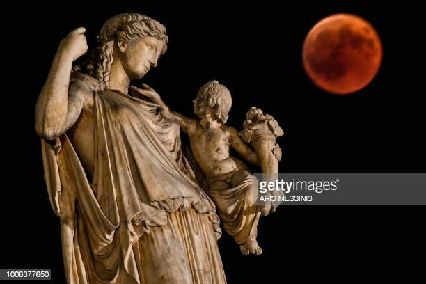 TOPSHOT View of the full moon during the blood moon next to the ancient Greek goddess Irine holding a child symblolising peace and justice in central...