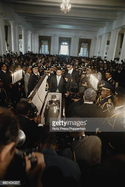 View of the funeral of Francois Papa Doc Duvalier President of Haiti with his body placed in a glass covered open casket and mourned by his son and...
