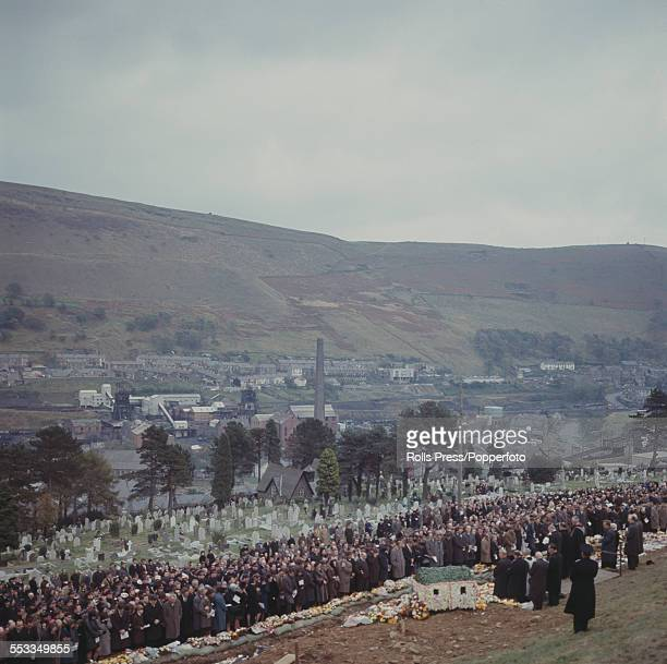 View of the funeral service for victims of the Aberfan disaster with mourners lining up in front of a communal grave on a hillside above the cemetery...