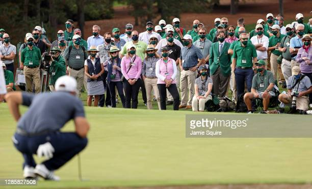 View of the gallery as Dustin Johnson of the United States lines up a putt on the 18th green during the final round of the Masters at Augusta...