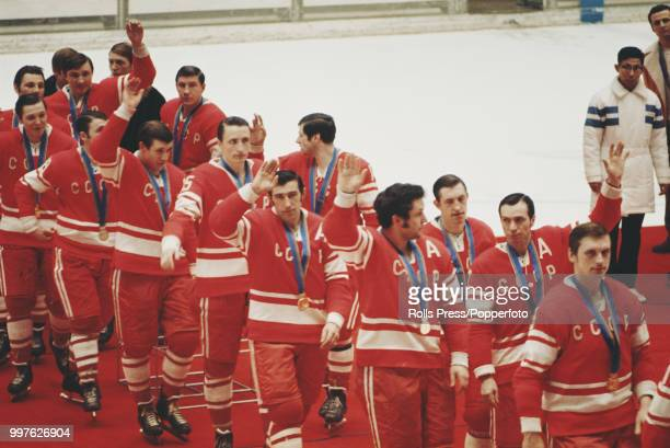 View of the gold medal winning Soviet Union ice hockey team pictured together walking off the medal podium after finishing in first place in the...