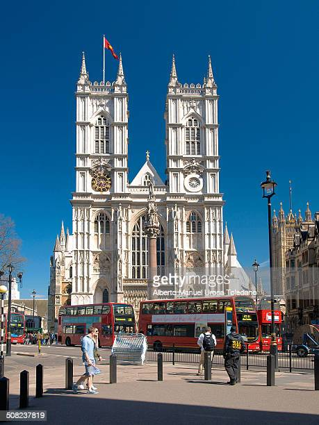 View of the gothic style Collegiate Church of St Peter at Westminster, commonly known as Westminter Abbey. There are a few double-deck buses.