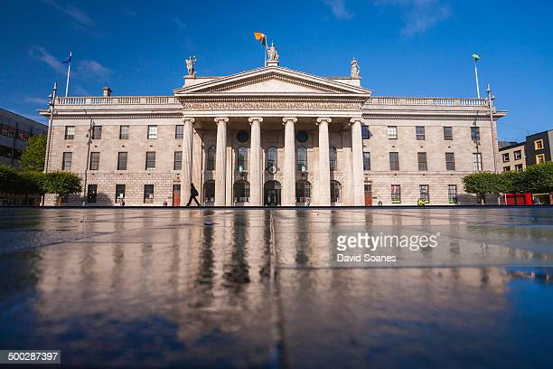 View of the GPO from the ground on a sunny morning with reflections of the building in the wet ground.