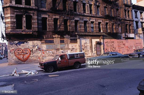 View of the graffiti-covered facade of an empty building in the Lower East Side neighborhood, New York, New York, 1990. Text at right reads 'Welcome...