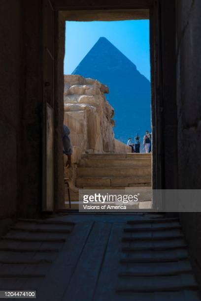 View of the Great Pyramids of Giza through narrow walkway, Cairo, Egypt.