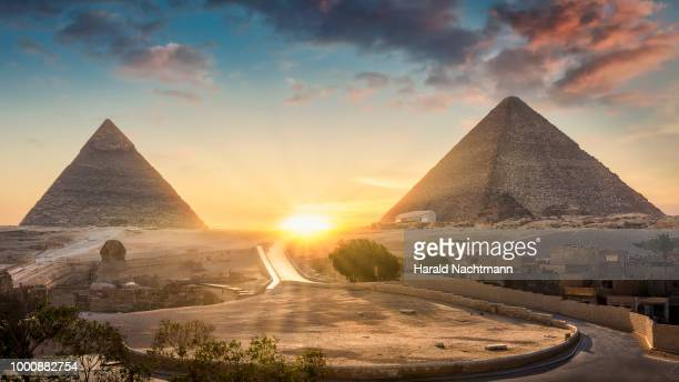 view of the great sphinx, pyramid of khafre and great pyramid of giza at sunset, cairo, giza, egypt - history stock pictures, royalty-free photos & images