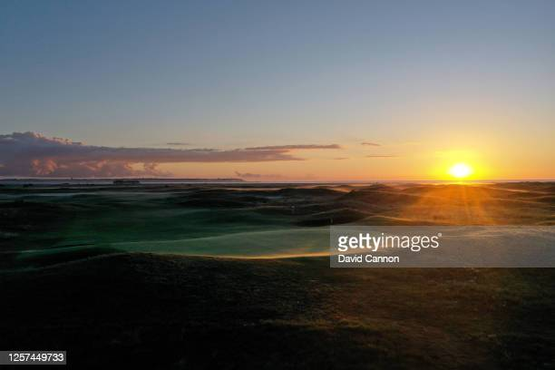 A view of the green on the par 4 17th hole as the sun rises behind at the host venue for the 2021 Open Championship at The Royal St George's Golf...