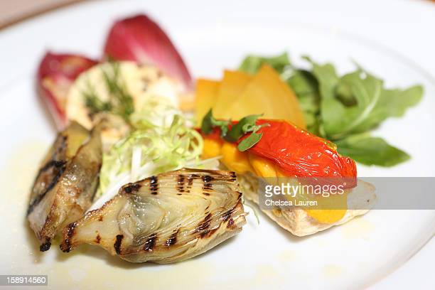 A view of the grilled artichoke with fennel tomato lemon mousse and California pepper honey goat cheese on endive pear salad appetizer prepared by...