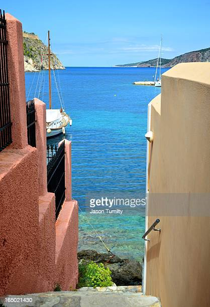 CONTENT] A view of the harbor and sea between two houses at Assos in Kefalonia Greece