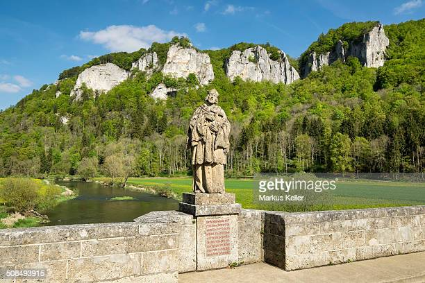 View of the Hausener Zinnen peaks and the statue of St. Nepomuk seen from Hausener Brucke bridge, Hausen im Tal, Upper Danube Valley, Baden-Wurttemberg, Germany