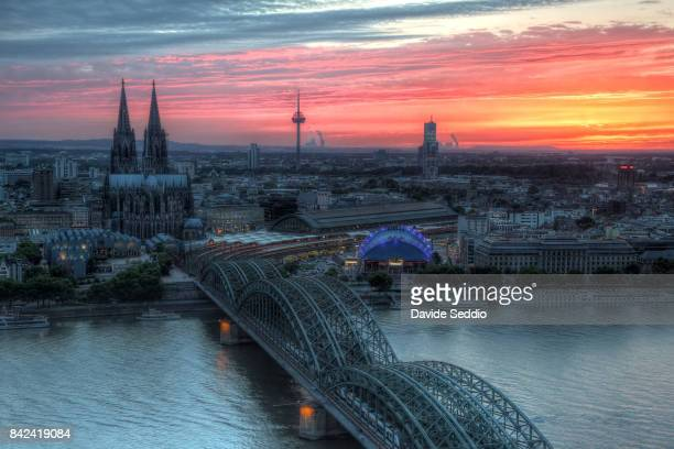 View of the Hohenzoller bridge and Cologne cathedral during the sunset
