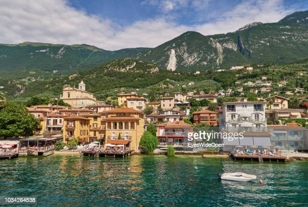 View of the houses hotels restaurants and mountains from a ferry boat at the northern part of the Lake Garda on June 29 2018 in Malcesine Italy
