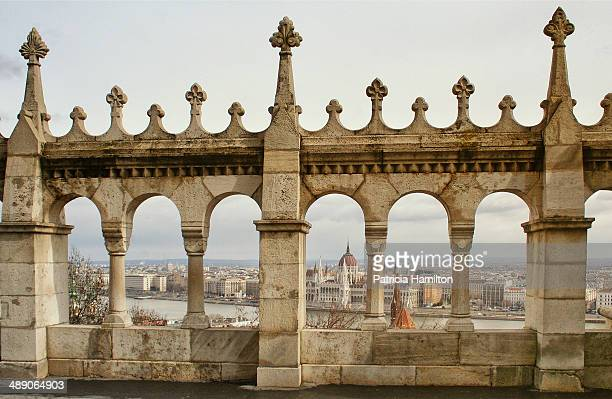 View of the Hungarian Parliament Building taken through the arches of the Fisherman's Bastion at Budapest. River Danube in the background.