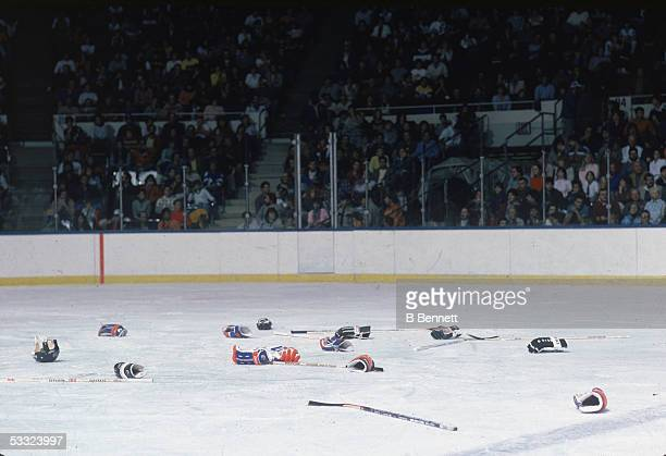 View of the ice littered with abandoned hockey gloves helmets and sticks after a fight between opposing teams 1980s
