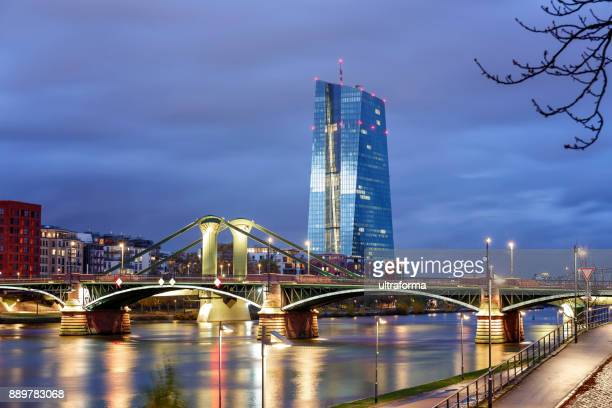 View of the illuminated Frankfurt am Main skyline with Flossen Brucke and European Central Bank at dusk