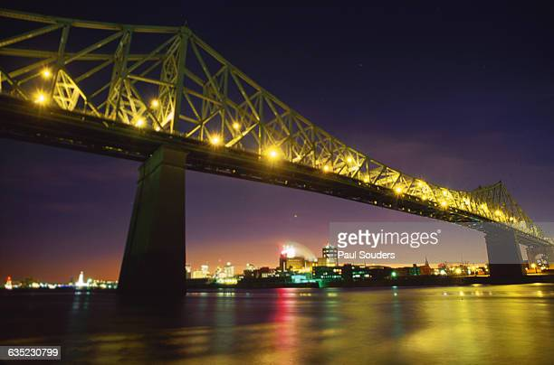 A view of the illuminated JacquesCartier Bridge at dusk The bridge spans the St Lawrence River in Montreal Quebec and the Ile SainteHelene islands...