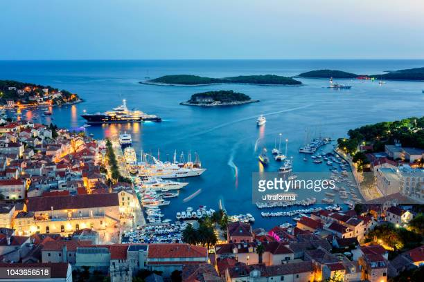 view of the illuminated old town hvar and the harbor with pakleni islands at dusk - hvar stock photos and pictures