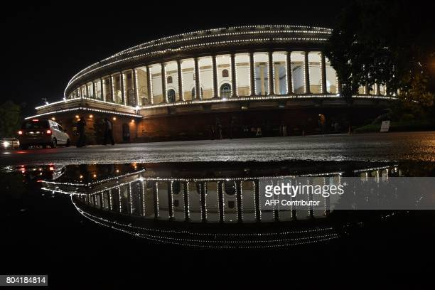 View of the Indian Parliament illuminated prior to a special session for the implementation of the new Goods and Services Tax regime in New Delhi on...