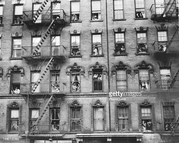 View of the inhabitants of a tenament house as they look out from their windows Newark New Jersey early 20th century The store on the ground floor is...
