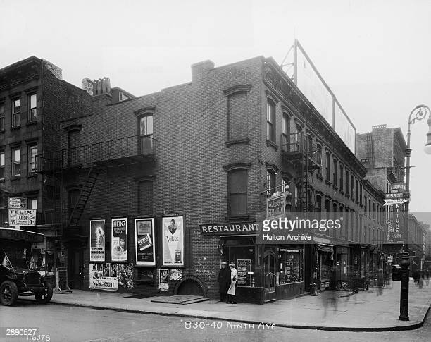 View of the intersection of West 55th Street 9th Avenue shows two men one in an apron and cap talking outside the Loving Restaurant in the center New...