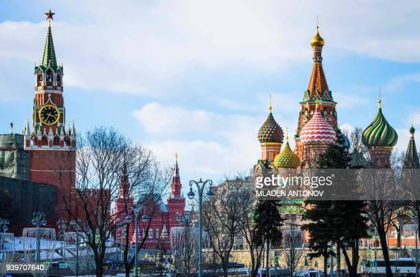 A view of the Kremlin's Spasskaya Tower the State Historical Museum and St Basil's Cathedral in Moscow on March 29 2018 At least 25 countries have...