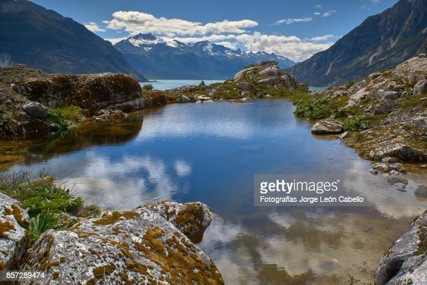 a view of the lake los leones from the rocky west shore next to the glacier. - glacier lagoon stock photos and pictures