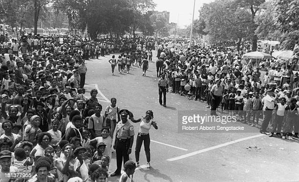 View of the large crowds and police officers during the annual Bud Billiken parade, sponsored by the Chicago Defender, Chicago, Illinois, 1984.