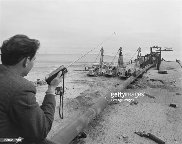 View of the launch site of the North Coates pipeline, showing a man in the foreground holding a two-way radio. The civil engineering work on the...