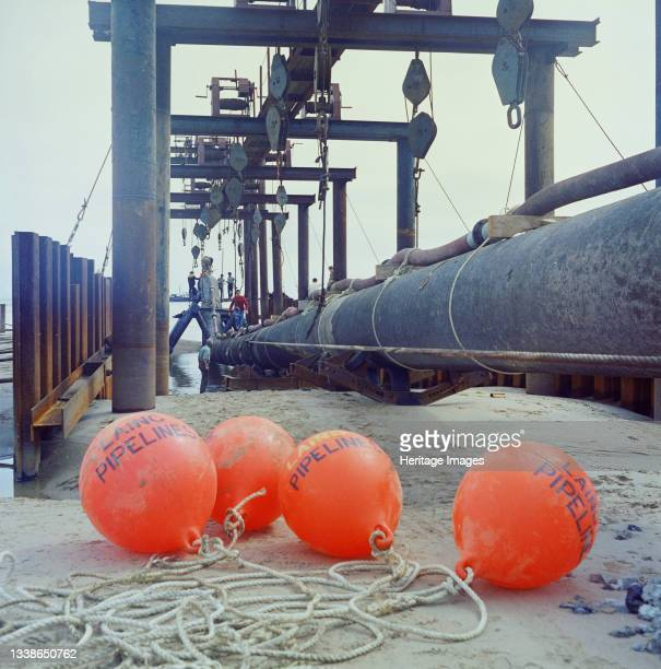 View of the launch site of the North Coates pipeline, showing Laing Pipelines buoys in the foreground with the pipeline and lifting equipment in the...