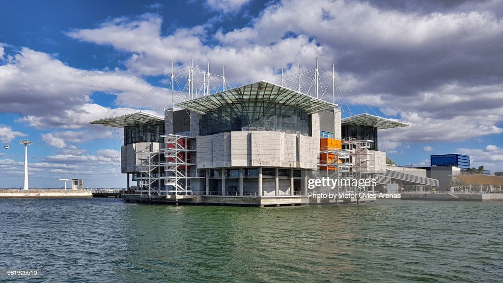 View of the Lisbon Oceanarium surrounded by the water of river Tagus and the cable car alongside the river in the background in the Parque das Naçoes in Lisbon, Portugal : Foto de stock