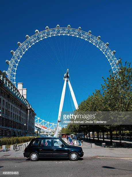 CONTENT] A view of the London Eye with a black cab in the foreground