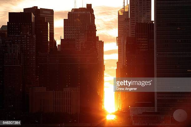 A view of the 'Manhattanhenge' sunset from Hunters Point South Park July 11 2016 in the Queens borough of New York City 'Manhattanhenge' is created...