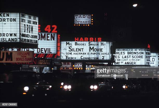 A view of the marquees of cinemas on West 42nd Street including the New Amsterdam Theatre Cine 42 the Harris Theater and the Liberty Theatre in 1976...