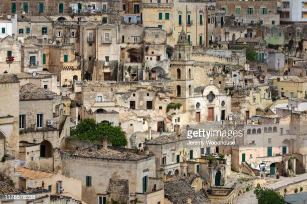 view of the matera showing the rupestrian church of san pietro barisano spotlit by the sun - jeremy woodhouse stock pictures, royalty-free photos & images