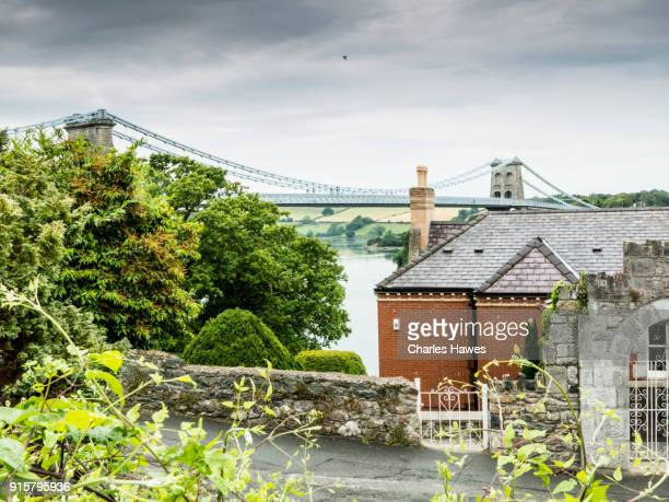 view of the menai suspension bridge (1826) designed by thomas telford from near bangor:the wales coast path - north wales - menai suspension bridge stock pictures, royalty-free photos & images