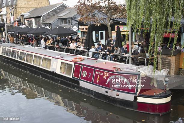 """View of the """"Merlin, """" the London Waterbus Company's red and cream, number seven, narrowboat, barge, or canal boat, docked next to crowds of people,..."""